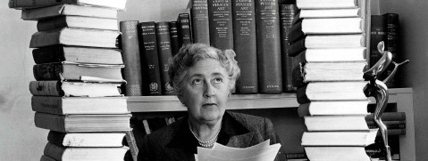 Volume 2, Page 114, Picture, 21, Literature Mystery author and writer, Agatha Christie, pictured at her home, Winter-Brook House, sitting behind her desk with books piled high (Photo by Popperfoto/Getty Images)